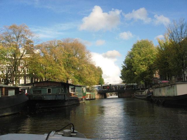 10月16日的下午,Hein老爷爷安排我们去坐船游阿姆斯特丹,毕竟最初这个城市和江南一样,也是以船为主要的交通工具。 小船是Hein老爷爷和他弟弟共有的。 Hein老爷爷的弟弟就住在这里,当然他自己对这片区域也是非常熟悉了,一路上总有人和他打招呼聊几句。据Hein老爷爷说这些建筑以前都是仓库,后来因为这里的码头的衰落,都被改建成了住宅。  老港口和船屋,荷兰有很多人都喜欢住在船屋里,甚至是船上,也成了荷兰运河的一道风景。  让人想到船的屋顶,窗户上映出的蓝天  小小的港口  Hein船长和他的小船,看上去